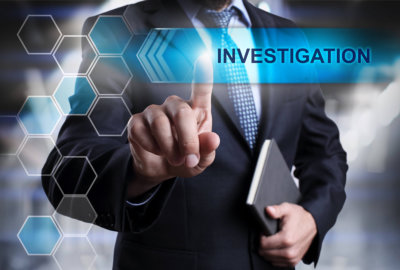 man pointing at investigation word