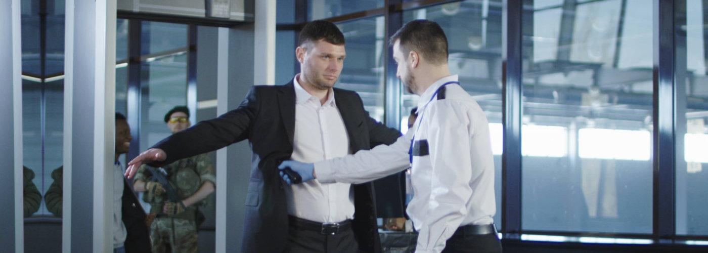 guard inspecting a man